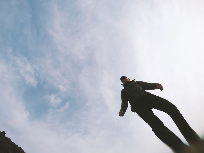 Low angle view of mature man standing against cloudy sky
