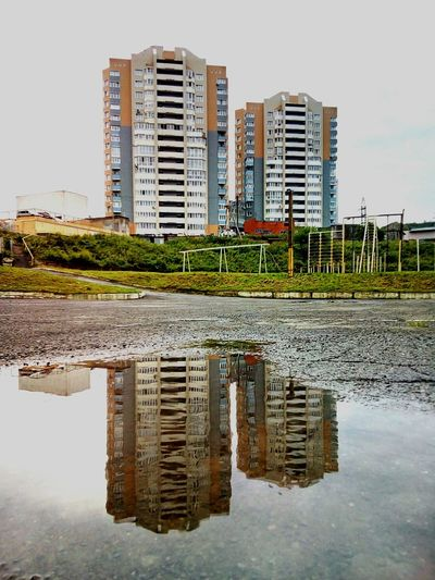 Buildings and their reflection in the puddle Buildings Puddle Puddleography Puddle Reflections Reflections Reflection Rain Rainwater Water Wet Asphalt City Cityscapes Cityscape Summer August Playground Sport Sports Equipment Day Cloudy