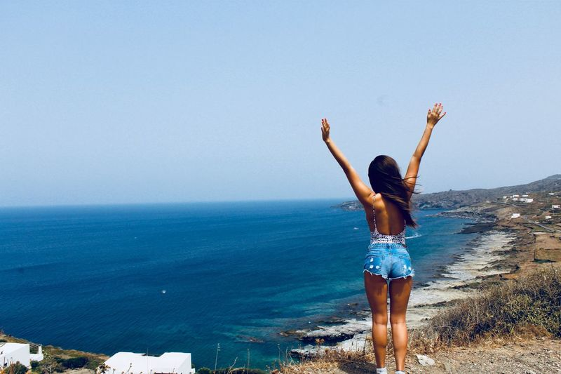 Woman with arms raised standing at beach against clear sky