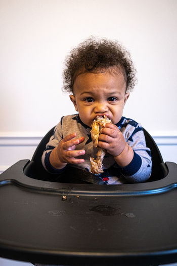 Portrait of baby boy eating chicken