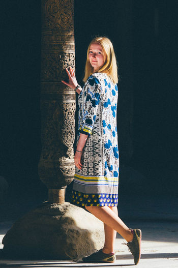 The blond girl standing near the old ancient  column. touch eternity