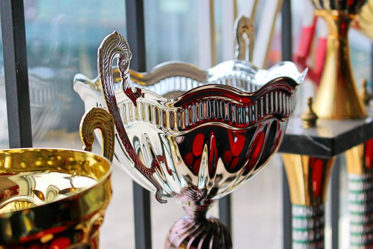 Close-up of trophies by window for sale