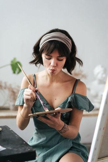 Female Painter Mixing Paint On Palette At Art Studio