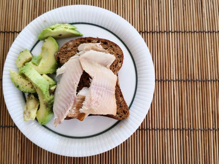 Omega 3 breakfast with avocado and trout fillet on bread copy space Trout Fillet Omega 3 Fatty Acids Omega 3 Studio Shot Plate Fruit Breakfast High Angle View SLICE Close-up Food And Drink Prepared Food Chopped Sandwich Avocado Garnish Bread Serving Dish Toasted Guacamole Spread Toasted Bread Wrap Sandwich