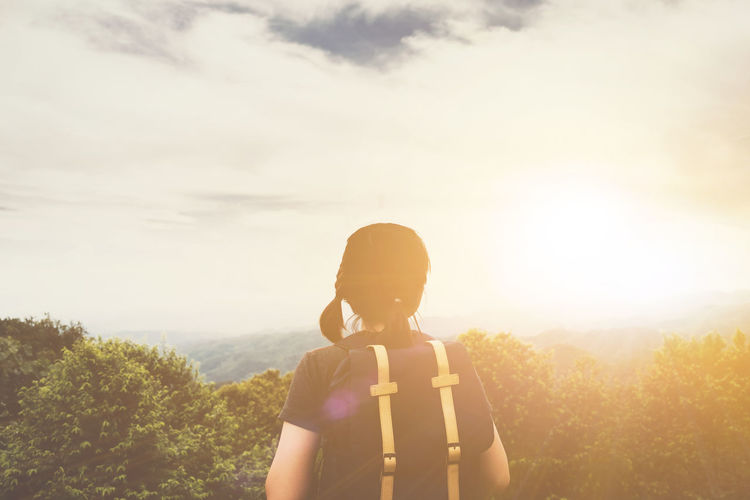 Hipster young girl with backpack enjoying sunset on peak of mountain. Tourist traveler on background landscape Backpacking Hiking Light Backpacker Growth Hipster Landscape Leisure Activity Mountain Nature One Person Outdoors Real People Sky Standing Sunrise Tree