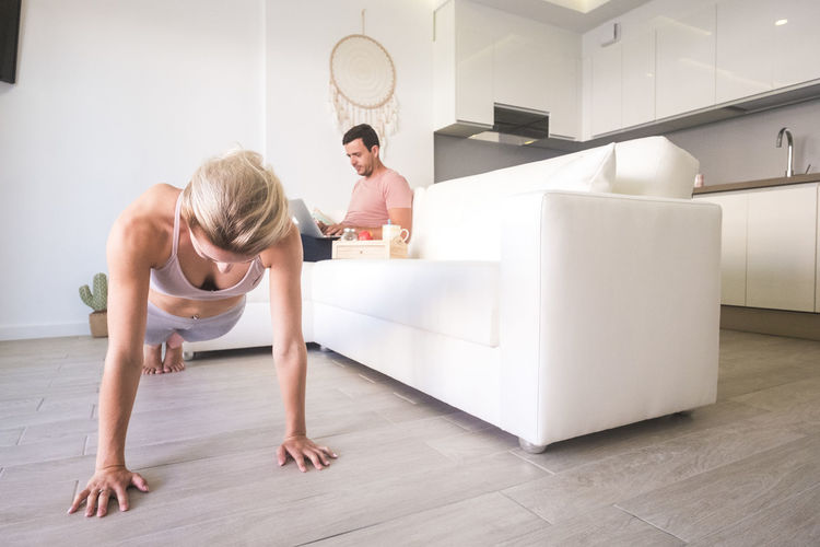 Woman exercising while man using laptop at home