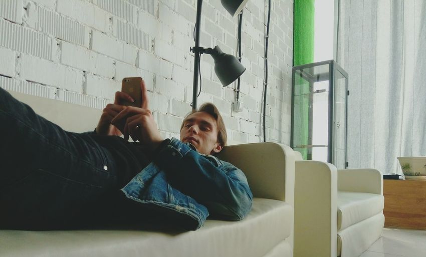 Man Using Phone While Relaxing On Sofa At Home