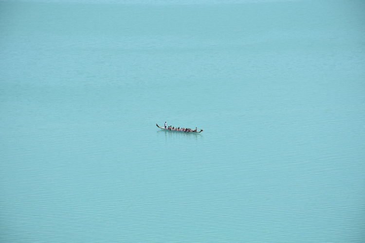Aerial View Of People Traveling In Boat On Sea