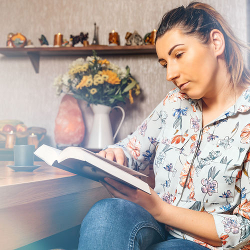 Young woman sitting on book at home
