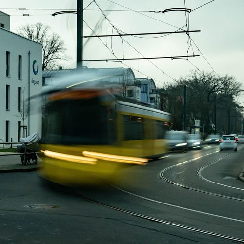 Blurred motion of train on road in city