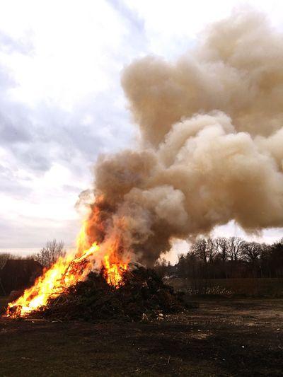 Bonfire on field against cloudy sky