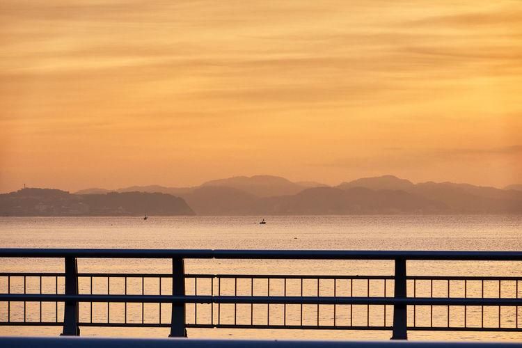 Scenic view of sea against orange sky during sunrise