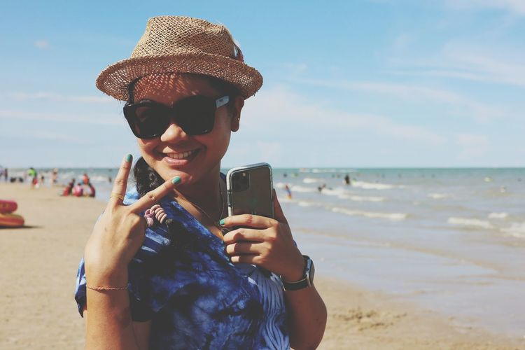 Portrait of mature woman holding mobile phone at beach