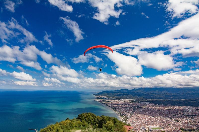 Parachute Flying Over Cityscape And Sea Against Cloudy Sky
