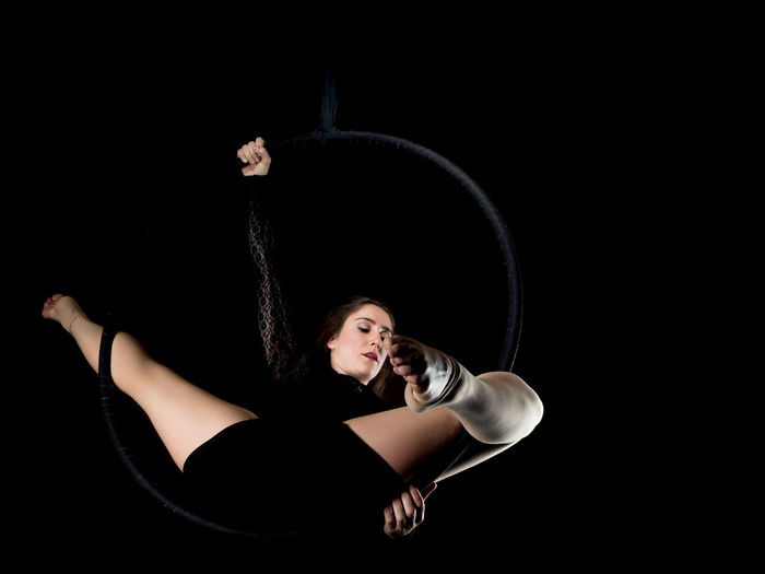 Young woman hanging over black background