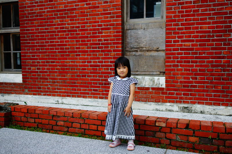 Portrait Of Girl Standing Against Red Brick Wall