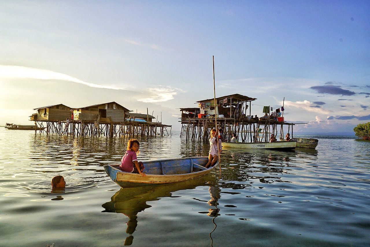 water, architecture, built structure, building exterior, sky, stilt house, nautical vessel, outdoors, real people, day, transportation, tranquility, rear view, waterfront, men, nature, full length, vacations, beauty in nature, sea, women, one person, oar, adult, people