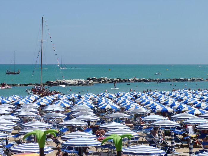 Blue umbrellas at beach against clear sky