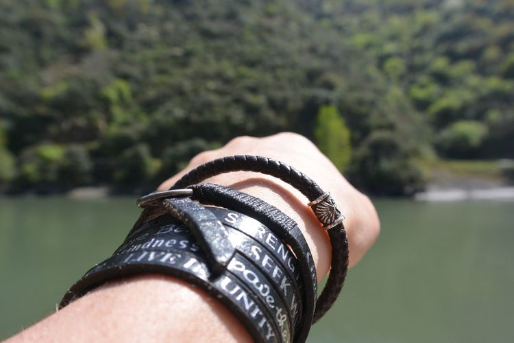 Cropped hand with black bracelets against river on sunny day