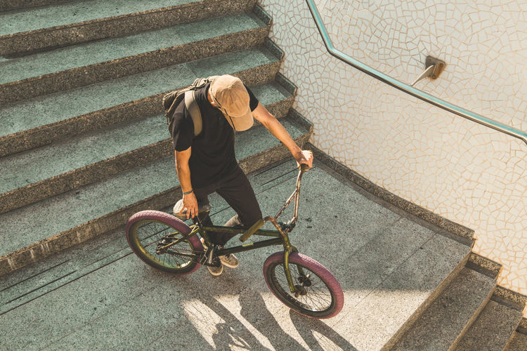 High angle view of man riding bicycle on staircase
