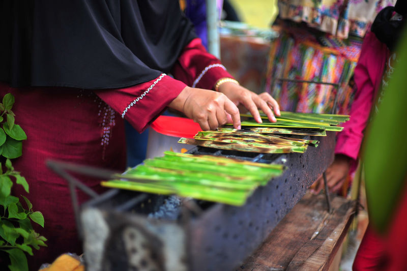 Midsection Of Woman Arranging Leaves On Metal Grate During Traditional Festival
