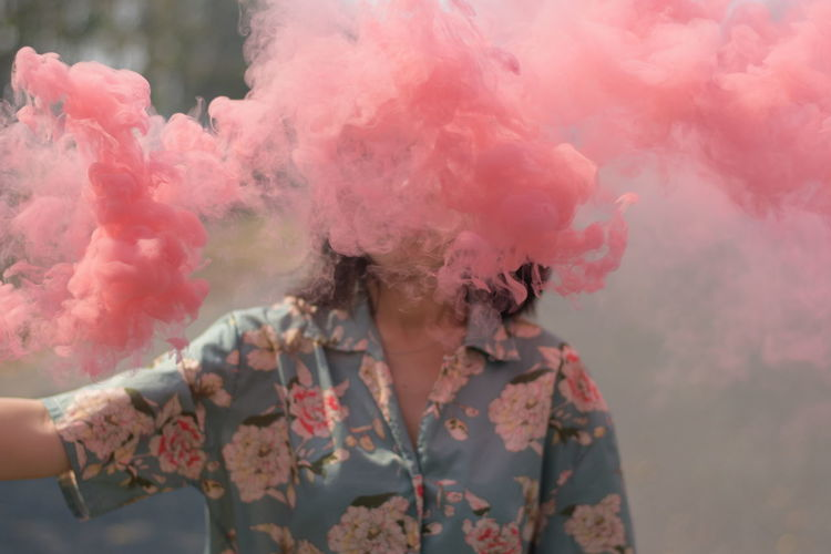 Close-up of man amidst pink smoke