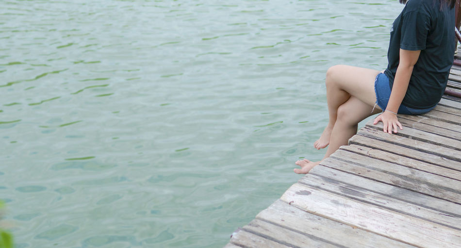 Low section of man sitting on pier over lake