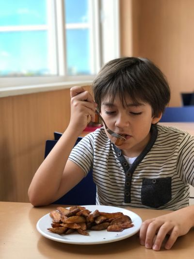 Boy eating potato chips while sitting on chair at restaurant