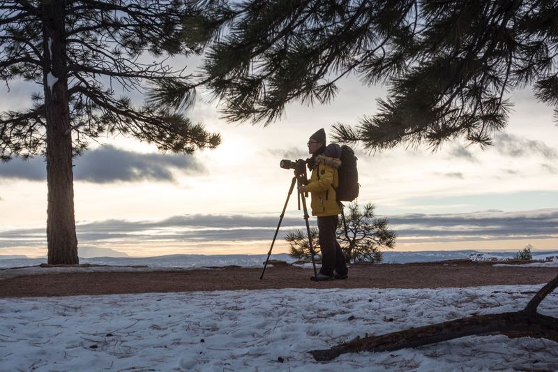 Cold Temperature One Person Holding Winter Full Length Sky Nature Tripod Outdoors Cloud - Sky Snow Real People Only Men Adults Only Day People One Man Only Adult