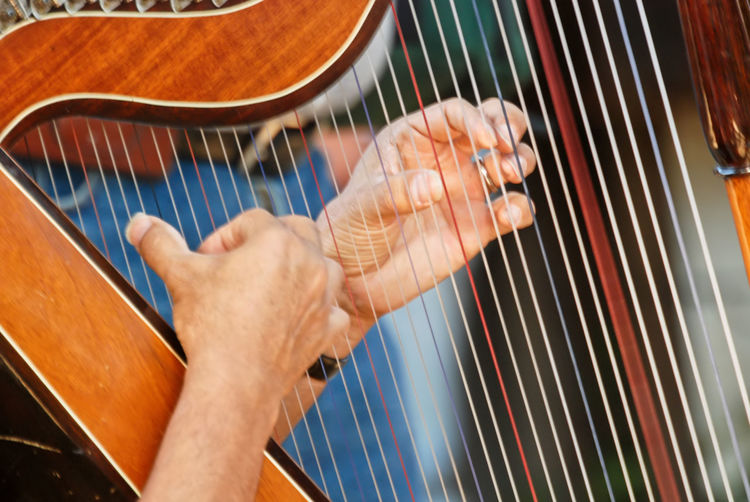 Close-up shot of man hands playing harp outdoors in santiago, chile. concept of music, and  leisure