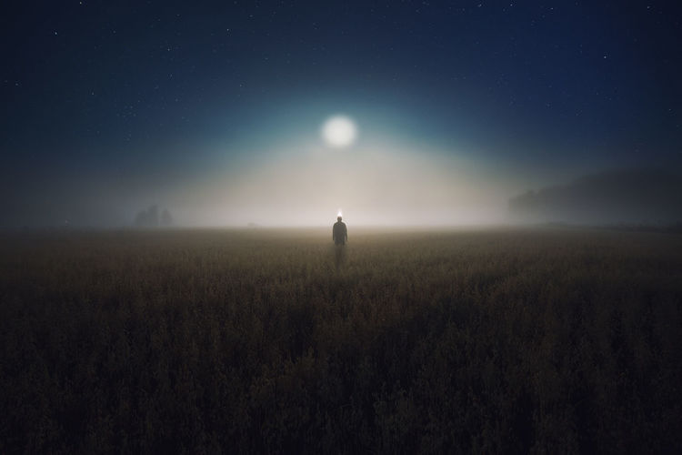Person standing on field against sky at night during foggy weather