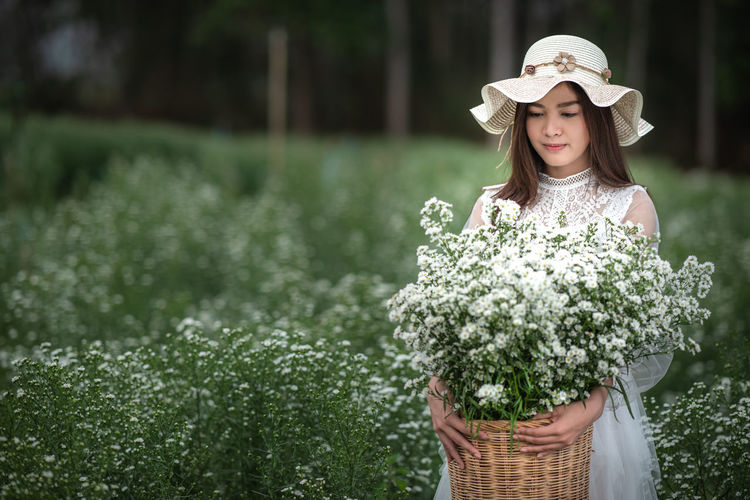 Beautiful girl with flowers Beautiful Girl Flower Plant Flowering Plant One Person Hat Clothing Standing Women Day Adult Young Adult Young Women Nature Holding Beauty In Nature Real People Leisure Activity Waist Up Beautiful Woman Sun Hat Outdoors Hairstyle Flower Arrangement Bouquet