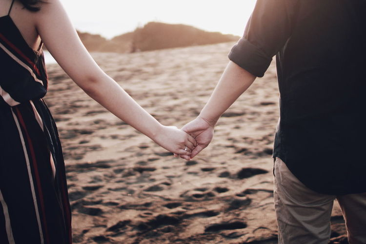 Midsection of couple holding hands standing at beach