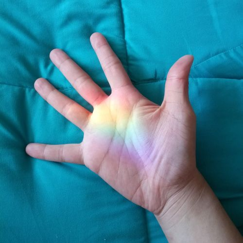 Close-up of human hand with spectrum on duvet