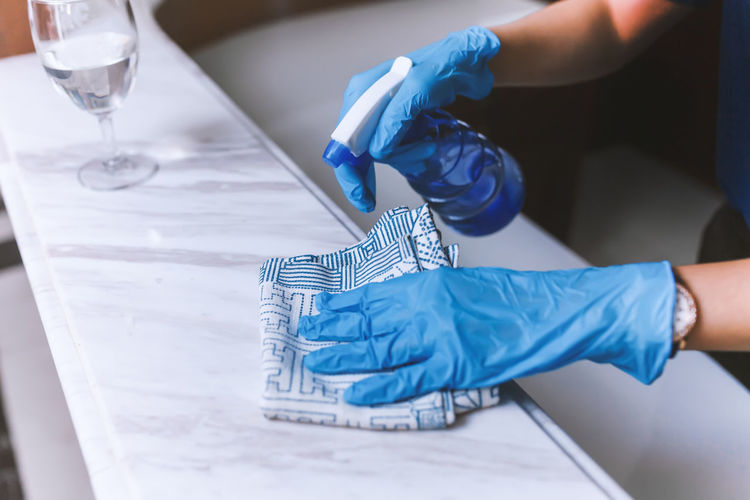 Cleaning home table sanitizing kitchen table surface with disinfectant spray bottle washing