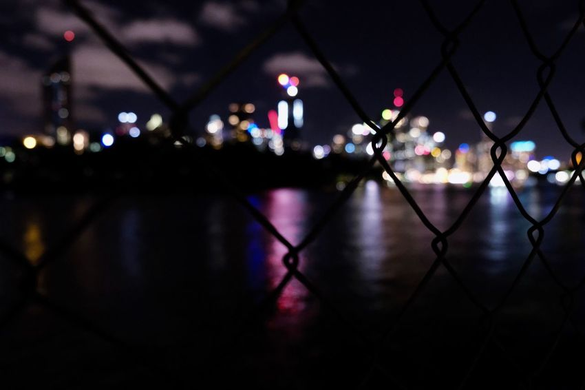 Twilight Night Illuminated Chainlink Fence Focus On Foreground Reflection No People Architecture Close-up Outdoors City Water Building Exterior Defocused