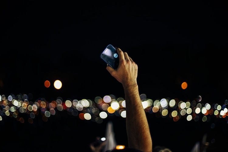 Midsection of person holding smart phone at night