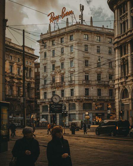 People on city street by buildings against sky