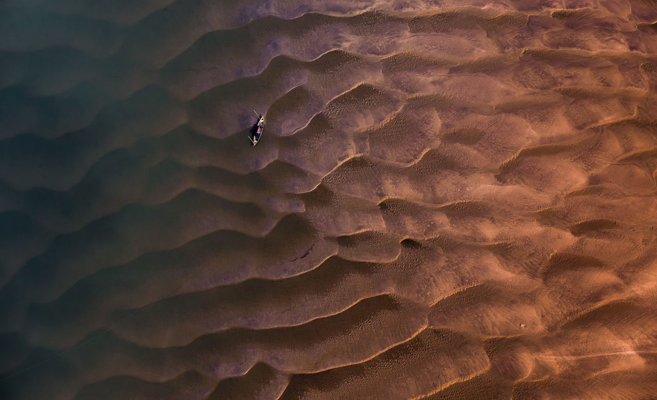 AERIAL VIEW OF BOAT ON RIPPLED WATER