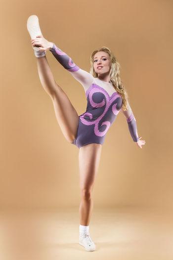 Portrait Of Female Gymnast Stretching Against Orange Background