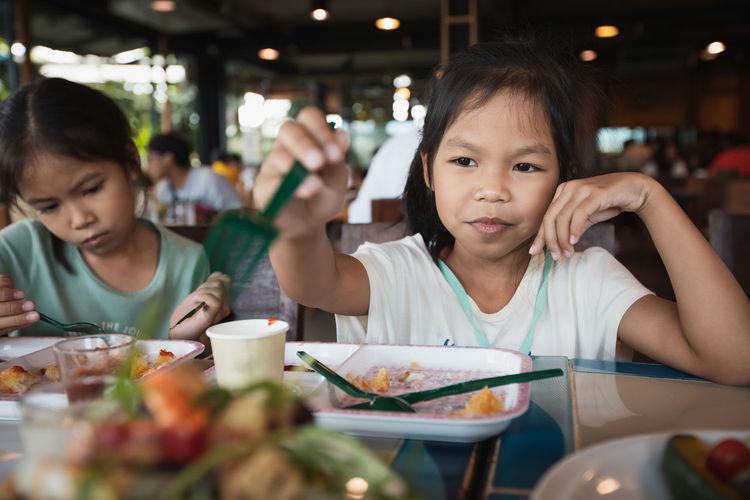 Portrait of cute girl eating food in restaurant