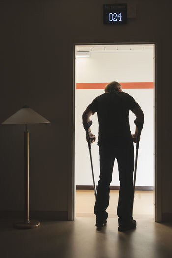 Rear view of silhouette man standing at home