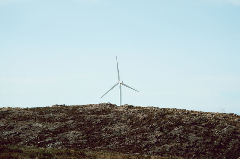 Low angle view of wind turbines on hill against sky