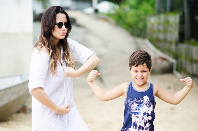 Happy mother with son flexing muscles while standing on street