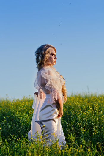 Side View Of Bride Standing On Grassy Field Against Blue Sky
