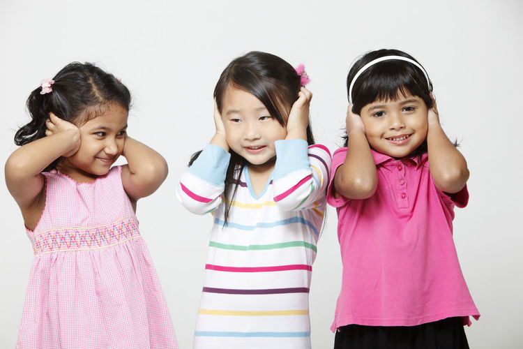 young girls of malaysia three major race malay chinese and indian Happiness Indian Innocence Bff Casual Clothing Cheerful Child Childhood Chinese Covering Ears Cute Elementary Age Friendship Front View Funny Faces Harmony Malay Malaysia Mixed Race Multiracial  Playful Portrait Studio Shot Three People Waist Up