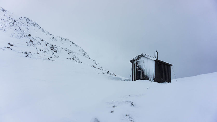 Hut on snow covered mountain against sky