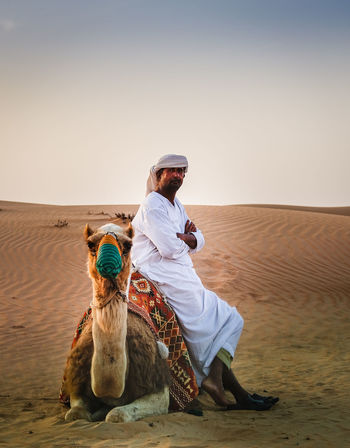 Animal Themes Casual Clothing Clear Sky Copy Space Desert Domestic Animals Dromedary Full Length Leisure Activity Lifestyles Mammal Men One Animal Person Real People Rear View Sand Sitting Young Adult Young Men