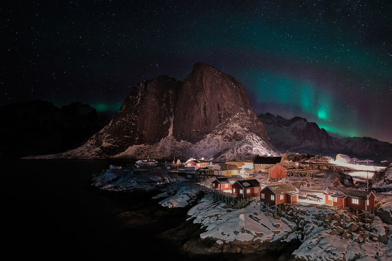 Illuminated buildings by mountain against sky at night