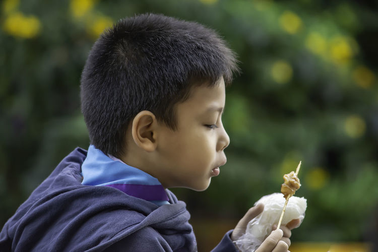 Side view of boy eating food at outdoors
